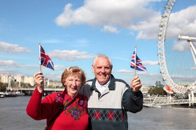 seniorní pár držící britské vlaječky
